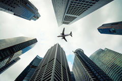 Singapore city buildings and a plane flying overhead in morning Royalty Free Stock Photo