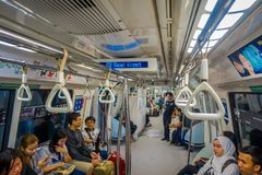 SINGAPORE CITY, SINGAPORE - NOV 13, 2013: Indoor view of rail commuters ride a crowded Mass Rapid Transit MRT train Royalty Free Stock Photography