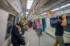 SINGAPORE CITY, SINGAPORE - NOV 13, 2013: Indoor view of rail commuters ride a crowded Mass Rapid Transit MRT train Stock Photos