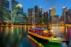 Singapore city. Skyline. Excursion cruise boat and business district view. downtown reflected in water at dusk in Marina Bay. Travel cityscape royalty free stock photography