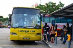 Singapore coach terminal for bus transport to Johor Bahru Malaysia. Singapore - January 7, 2015: Travelers mill around a yellow Malaysian registered coach Stock Photos