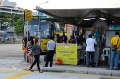 Singapore coach terminal for bus transport to Johor Bahru Malaysia. Singapore - January 7, 2015: Travelers mill around a yellow Malaysian registered coach Royalty Free Stock Photography