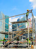 Singapore construction site. SINGAPORE - MAY 09, 2013: Workers at construction site in front of Singapore downtown in Singapore. Construction industry is Stock Photography
