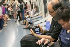 Tourist secretly taking photograph of people on Singapore underg Stock Photo