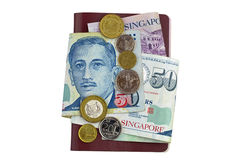 Singapore dollar banknote and coins on Passport isolated on whit. Singapore dollar banknote SGD and coins on red brown Passport isolated on white background Stock Image