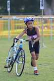 Singapore Duathlon 2012. A kid participant in the Singapore Duathlon 2012, held in East Coast Park, pushing the bike back to the transition area for the last Royalty Free Stock Image
