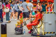 SINGAPORE SINGAPORE - FEBRUARI 01, 2018: Äldre gatamusiker som busking längs en upptagen gata under kinesiskt nytt år in royaltyfria foton