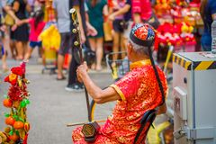 SINGAPORE SINGAPORE - FEBRUARI 01, 2018: Äldre gatamusiker som busking längs en upptagen gata under kinesiskt nytt år in fotografering för bildbyråer