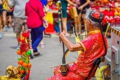 SINGAPORE SINGAPORE - FEBRUARI 01, 2018: Äldre gatamusiker som busking längs en upptagen gata under kinesiskt nytt år in arkivfoton