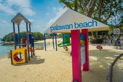 SINGAPORE, SINGAPORE - FEBRUARI 01, 2018: Niet geïdentificeerde mensen die in het strand en het informatieve teken met roze lopen Stock Afbeeldingen