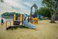 SINGAPORE, SINGAPORE - FEBRUARI 01, 2018: Niet geïdentificeerde mensen met hun die kind in een speelplaats in het strand binnen w Stock Foto