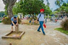 SINGAPORE SINGAPORE - FEBRUARI 01, 2018: Oidentifierat folk som framme går av många barn som spelar i vattnet Arkivfoton