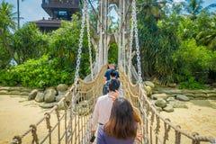 SINGAPORE SINGAPORE - FEBRUARI 01, 2018: Oidentifierat folk som går över en träupphängningspång över havet Royaltyfri Foto