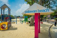 SINGAPORE, SINGAPORE - FEBRUARY 01, 2018: Gorgeous blue day and unidentified people walking in the beach and informative. Sign with pink columns in Palawan Stock Image