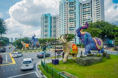 SINGAPORE, SINGAPORE - FEBRUARY 01, 2018: Outdoor view of unidentified people walking in the streets with some cars and. Huge stoned colorful elephants located Stock Photos