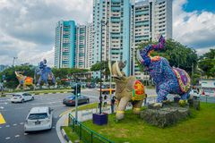 SINGAPORE, SINGAPORE - FEBRUARY 01, 2018: Outdoor view of unidentified people walking in the streets with some cars and. Huge stoned colorful elephants located Stock Image