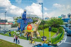 SINGAPORE, SINGAPORE - FEBRUARY 01, 2018: Outdoor view of unidentified people walking in the streets with some cars and. Huge stoned colorful elephants located Royalty Free Stock Images