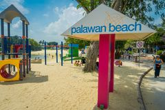 SINGAPORE, SINGAPORE - FEBRUARY 01, 2018: Unidentified people walking in the beach and informative sign with pink. Columns in Palawan Beach at Sentosa Island Royalty Free Stock Images