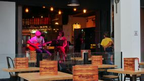 Young man and woman perform a song at Warehouse on Clarke Quay in Singapore stock video