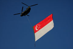 Singapore flag lifted by Chinook Royalty Free Stock Photos