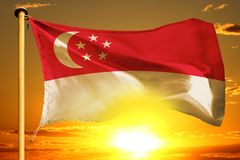 Singapore flag weaving on the beautiful orange sunset with clouds background. Singapore flag weaving on the beautiful orange sunset background stock images