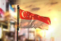 Singapore flagga mot suddig bakgrund för stad på soluppgång Backli Arkivbild