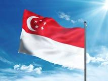 Singapore flagga som vinkar i den blåa himlen Arkivfoto