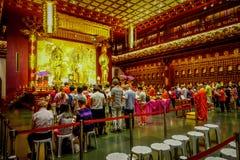SINGAPORE, SINGAPORE - 30 GENNAIO 2018: Gente non identificata che prega alla statua di signore Buddha dentro la reliquia del den Immagine Stock
