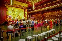 SINGAPORE, SINGAPORE - 30 GENNAIO 2018: Gente non identificata che prega alla statua di signore Buddha dentro la reliquia del den Fotografia Stock