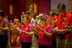 SINGAPORE, SINGAPORE - 30 GENNAIO 2018: Gente non identificata che tiene in loro piccoli libri delle mani e che canta al signore Fotografia Stock
