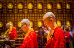 SINGAPORE, SINGAPORE - 30 GENNAIO 2018: Ritratto di giovani monaci che pregano alla statua di signore Buddha dentro il dente di B Immagine Stock Libera da Diritti