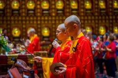 SINGAPORE, SINGAPORE - 30 GENNAIO 2018: Ritratto di giovani monaci che pregano alla statua di signore Buddha dentro il dente di B Immagine Stock