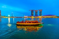 Singapore Harbor Skyline. Skyline of Singapore with cruise sails in the harbor at blue hour. Tourist boat on foreground. Night scene waterfront in marina bay Royalty Free Stock Photography