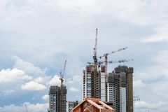 Singapore High rise tower with crane under construction. High rise tower crane and new unfinished residential townhouse under construction, buildings front view Stock Photography