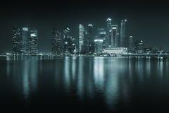 Singapore horisont på natten - skyskrapor med reflexioner. Arkivfoto