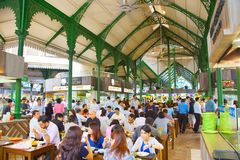 People indoor food court. Singapore. SINGAPORE - JAN 16, 2017 : People at popular food court in Singapore. Inexpensive food stalls are numerous in the city so stock image