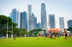 Amateur rugby match. Singapore downtown. SINGAPORE - JAN 16, 2017: Two amateur rugby team play rugby in Singapore. Singapore Downtown on te background royalty free stock image