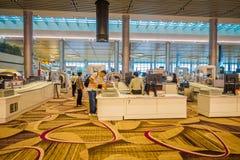 SINGAPORE SINGAPORE - JANUARI 30, 2018: En handelsresande köar på passkontroll på Singapore den internationella flygplatsen, in Arkivbild
