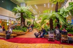 SINGAPORE SINGAPORE - JANUARI 30, 2018: Inomhus sikt av oidentifierat folk som sitter i stolar i en liten trädgård med Royaltyfria Bilder