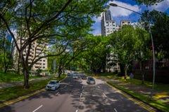 SINGAPORE, SINGAPORE - JANUARI 30 2018: Mooie openluchtmening van vele auto's in weg het omringen van vegetatie bij Stock Fotografie