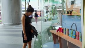 Tourist looking handbags on store window. Singapore - January 08, 2018: Female tourist looking handbags and accessories on store window at Orchard Road Singapore stock video