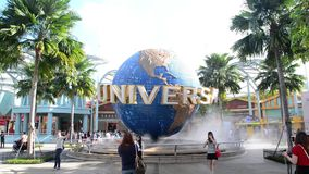 SINGAPORE - JANUARY 13 Tourists and theme park visitors taking pictures of the large rotating globe fountain in front of Universal stock footage