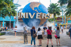 SINGAPORE - JANUARY 13 Tourists and theme park visitors taking pictures of the large rotating globe fountain in front of Universal Stock Images
