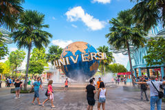 SINGAPORE - JANUARY 13 Tourists and theme park visitors taking pictures of the large rotating globe fountain in front of Universal Royalty Free Stock Photo