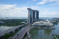 SINGAPORE - JULI 23rd, 2016: den unika skyskrapan i i stadens centrum Marina Bay med en kasino och en oändlighet slår samman över Arkivfoto