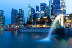 Singapore - July 15: Merlion fountain at dusk, July 15, 2013. Merlion Fountain and Central Business District (CBD) on the background, Singapore royalty free stock photo