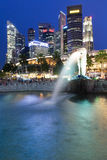 Singapore - July 15: Merlion fountain at dusk, July 15, 2013. Merlion Fountain and Central Business District (CBD) on the background, Singapore royalty free stock image