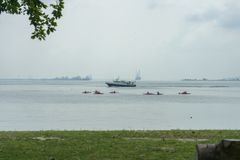 Ferry behind canoes in the strait royalty free stock photos