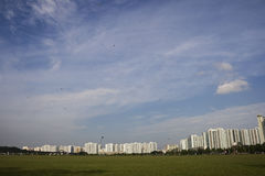 Singapore Landscpae. A Singapore landscape with a green grass field in front ground. People are flying kite there Stock Photo