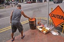 Singapore 28 08 2017 - Man med offer- bränning och att erbjuda på gatan på den kinesiska festivalen för ande för spökefestival royaltyfri fotografi